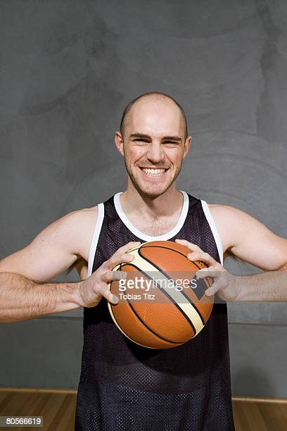 A young man holding a basketball preparing to throw it