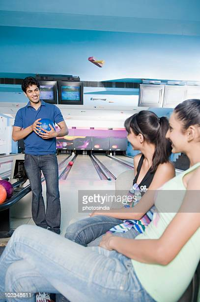 Young man holding a bowling ball and looking at two young women