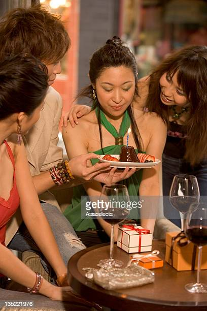 Young man holding a cake in a plate before three young women