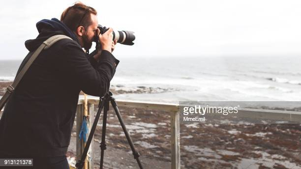 young man holding a camera on a tripod and taking a picture of the sea. gaspesie, quebec, canada - gaspe peninsula stock pictures, royalty-free photos & images