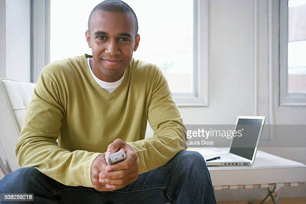 young man holding a cell phone, laptop computer in the background - laura belli foto e immagini stock