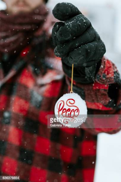 Young man holding a Christmas ball outdoor