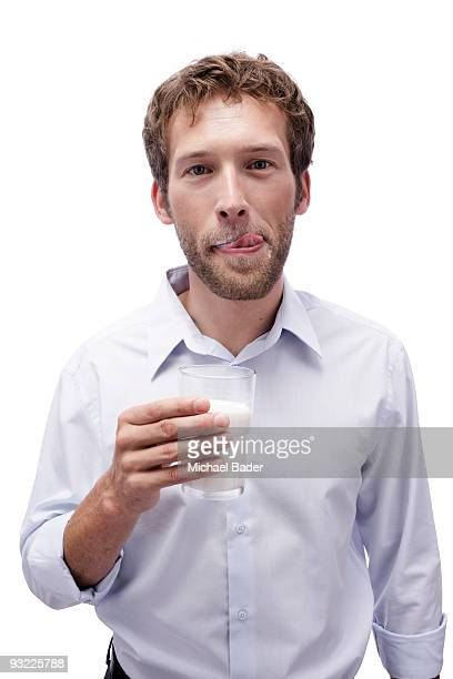 young man holding a glass of milk, portrait - lambendo os lábios - fotografias e filmes do acervo