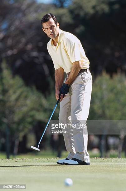 young man holding a golf club at a golf course - パットする ストックフォトと画像