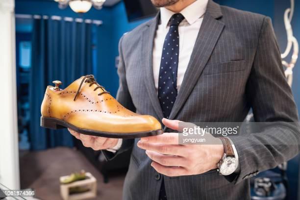 jonge man met een lederen schoen - nette schoen stockfoto's en -beelden