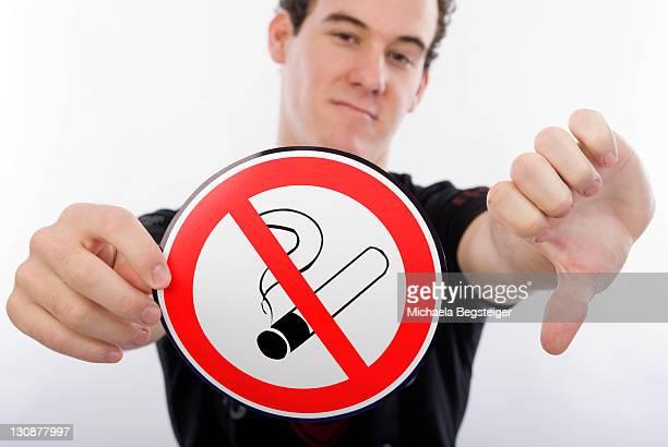 Young man holding a no smoking sign