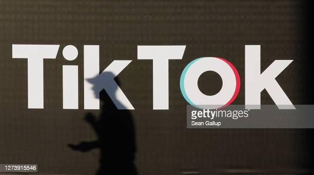 Young man holding a smartphone casts a shadow as he walks past an advertisement for social media company TikTok on September 21, 2020 in Berlin,...