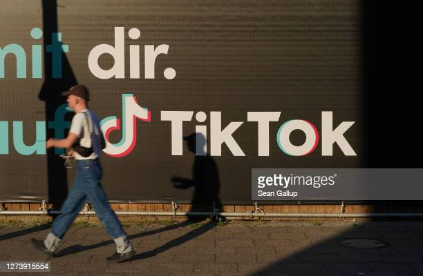Young man holding a smartphone walks past an advertisement for social media company TikTok on September 21, 2020 in Berlin, Germany. U.S. President...