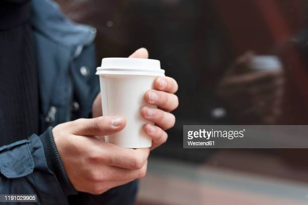 young man holding a takeaway coffee outdoors - テイクアウト ストックフォトと画像