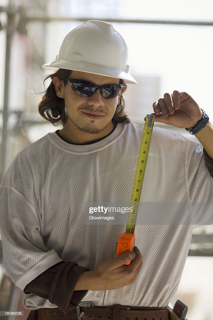 Young man holding a tape measure : Foto de stock