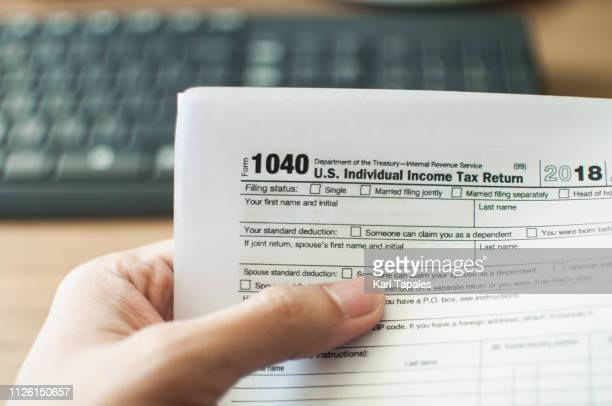 a young man holding a tax form - 1040 tax form stock photos and pictures