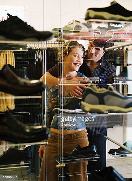 Young man holding a young woman in a shoe store