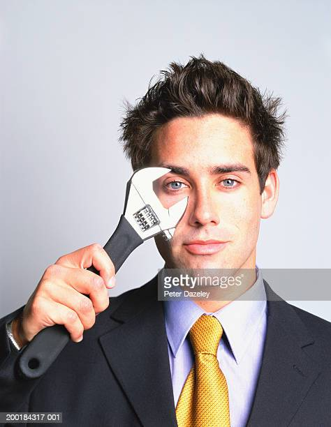 Young man holding adjustable spanner to eye, portrait