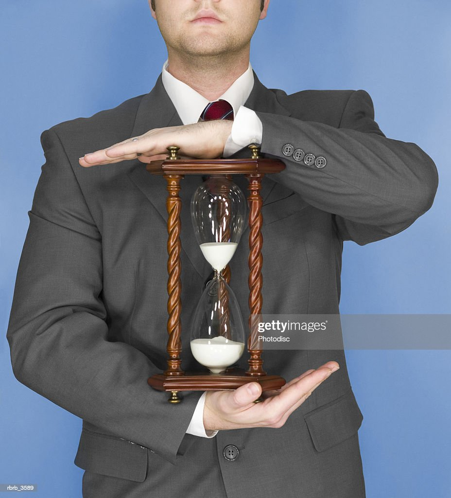 Young man holding an hourglass : Stockfoto