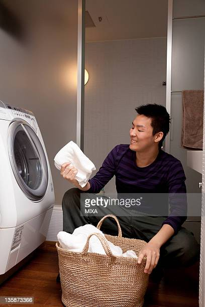 Young man holding and looking at towel in front of laundry machine