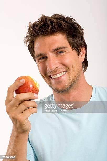 Young man holding apple, portrait, close-up