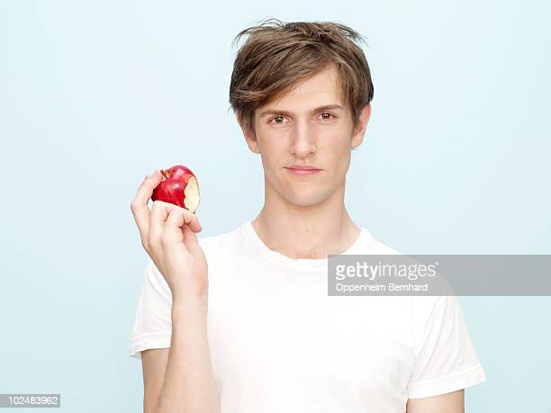 young man holding apple with bite out