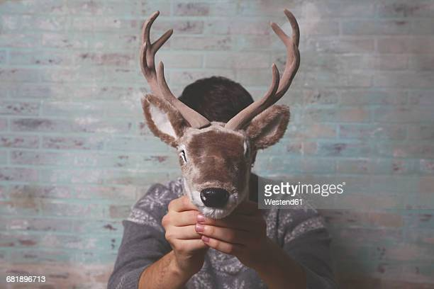 young man holding artificial deer head in front of his face - galhada - fotografias e filmes do acervo