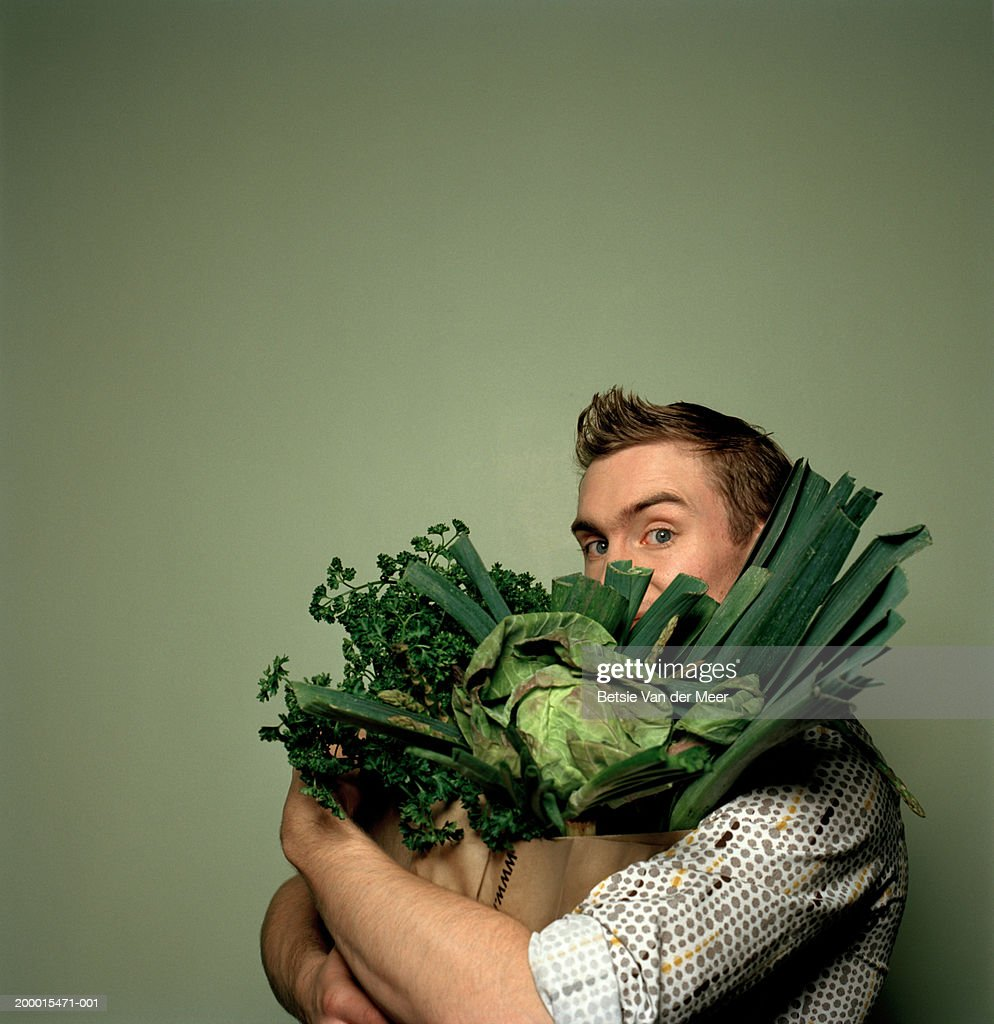 Young man holding bag full of vegetables, portrait : Stock Photo