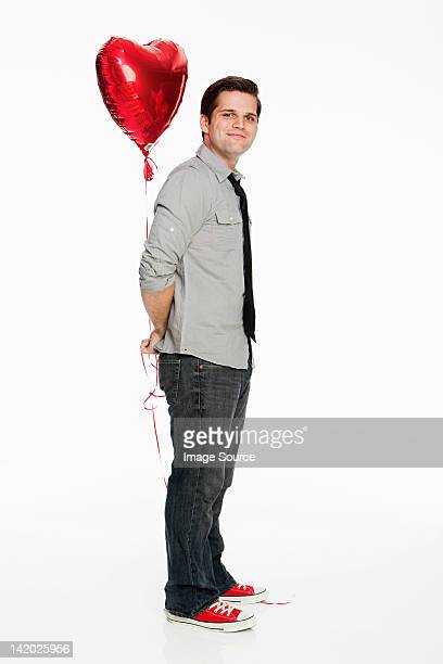Young man holding balloon against white background