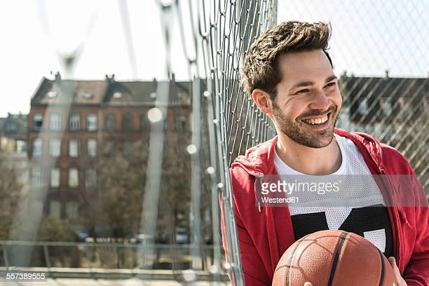 young man holding basket ball - basketball stadium stock-fotos und bilder