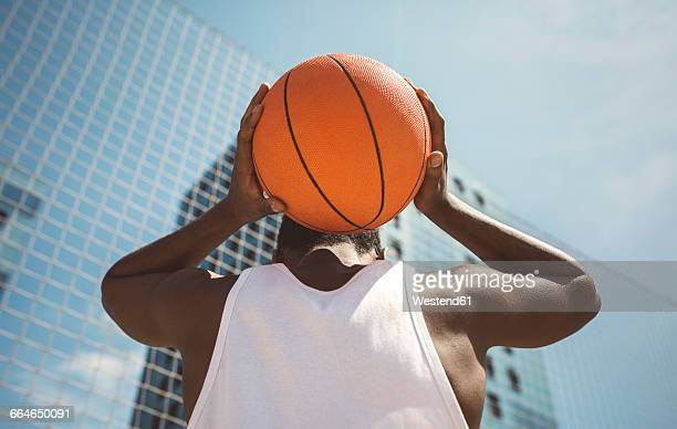 Young man holding basketball behind his head