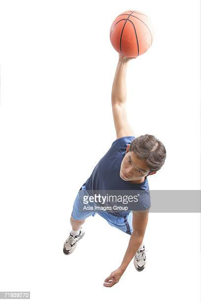 Young man holding basketball in one hand, jumping