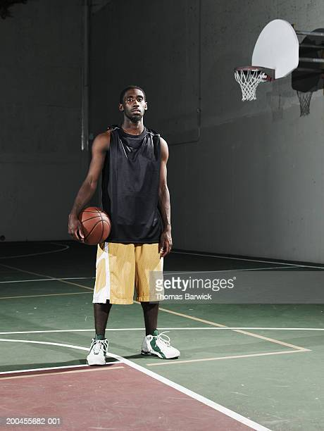 young man holding basketball on outdoor basketball court, night - basketball shoe stock photos and pictures