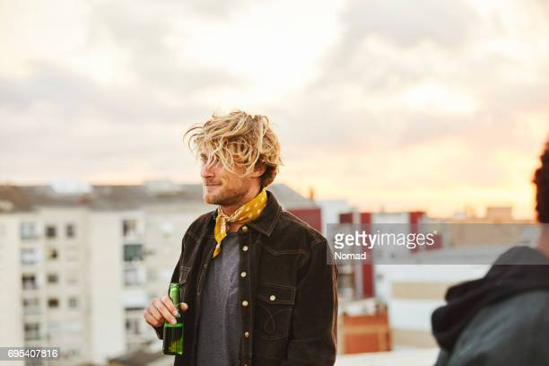 Young man holding beer bottle on terrace in city