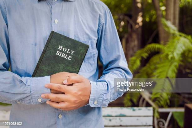 young man holding bible - christianity stock pictures, royalty-free photos & images