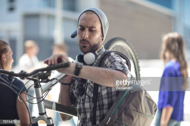 Young man holding bicycle checking the time