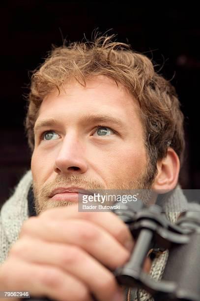'Young man holding binocular, close-up'