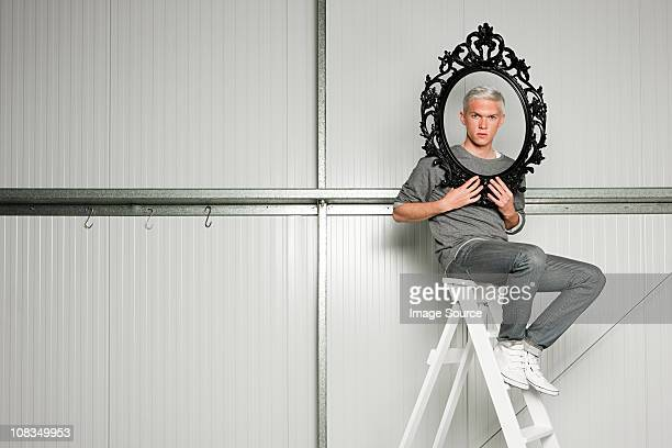 Young man holding black picture frame on stepladders