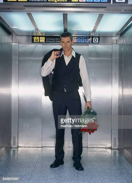 Young Man Holding Bouquet in Airport Lift