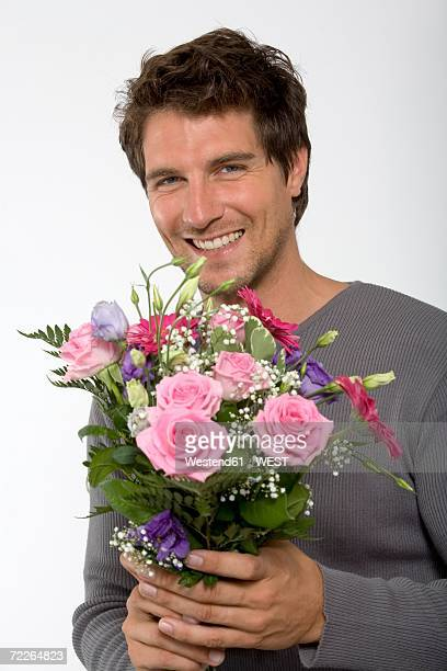 Young man holding bouquet of flowers, smiling, close-up, portrait