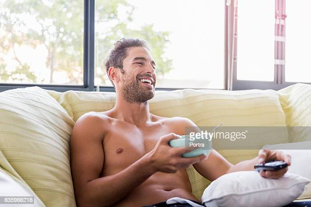 young man holding bowl while watching tv on sofa - halbbekleidet stock-fotos und bilder