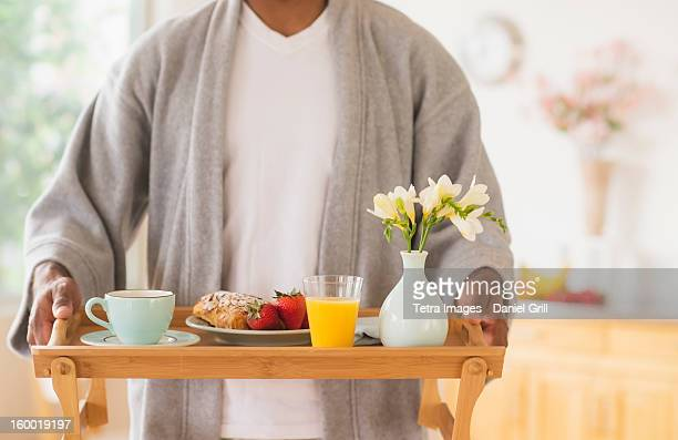 Young man holding breakfast tray