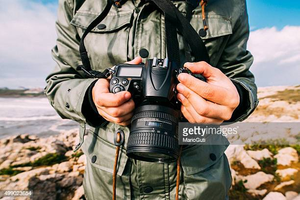 young man holding camera - photographer stock photos and pictures