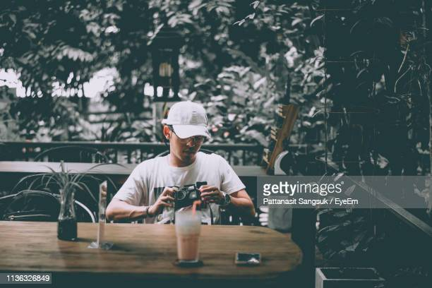young man holding camera while sitting on table - pattanasit stock pictures, royalty-free photos & images