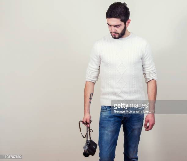 young man holding camera while standing against gray background - strap stock pictures, royalty-free photos & images