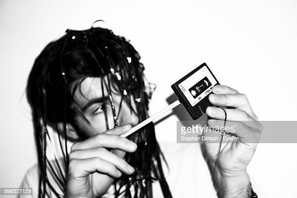 Young Man Holding Cassette While Sitting Against Wall At Home