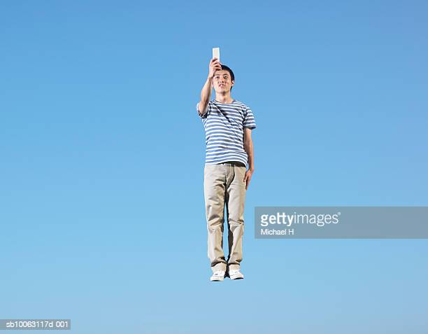 Young man holding cell phone jumping in blue sky