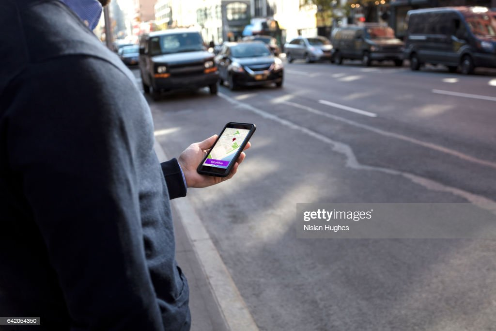 Young man holding cell phone waiting for car : Stock Photo