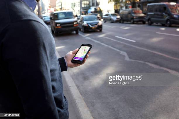 Young man holding cell phone waiting for car