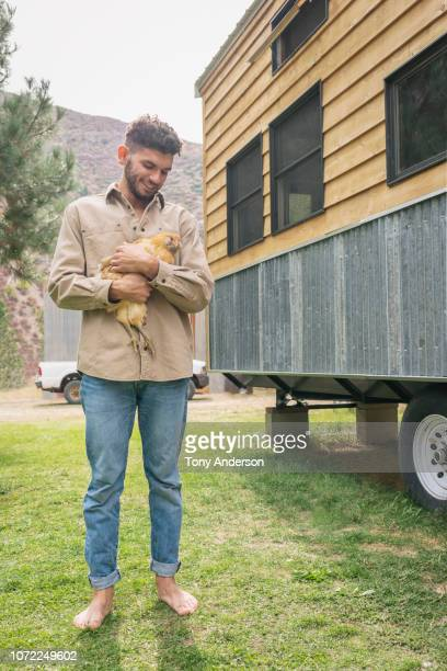 young man holding chicken outside tiny house - vorbeigehen stock pictures, royalty-free photos & images
