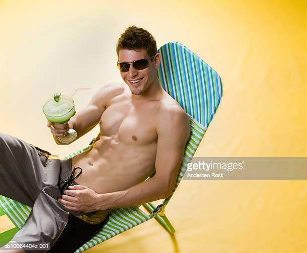 Young man holding cocktail, sitting on lounge chair in studio, elevated view, portrait