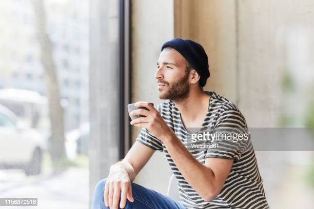 young man holding coffee cup at the window - só homens jovens imagens e fotografias de stock