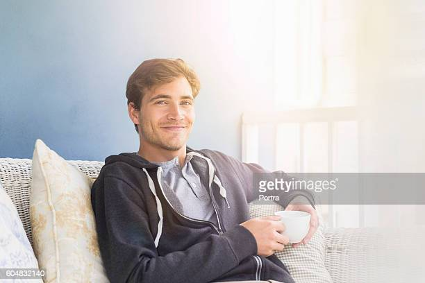 young man holding coffee cup while sitting on sofa - ein mann allein stock-fotos und bilder