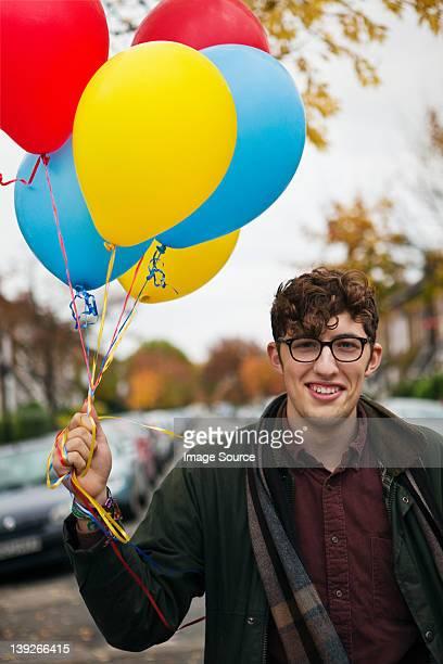 Junger Mann hält bunte Luftballons, Porträt