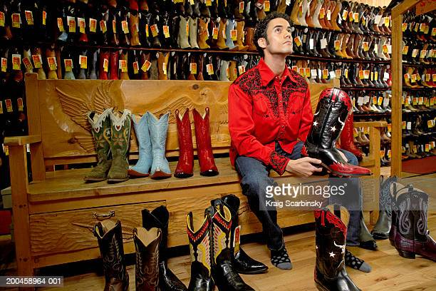 young man holding cowboy boot in shoe store, sitting on bench - cowboy boot stock pictures, royalty-free photos & images